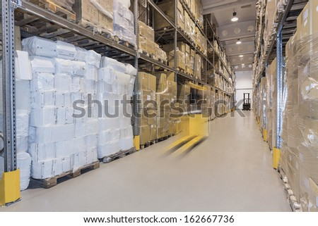 Yellow forklift moving in huge spacious warehouse - stock photo