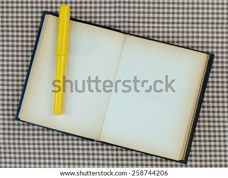 yellow fountain pen and old white notebook open on fabric - stock photo