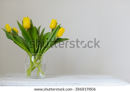 Yellow, fresh tulips in a vase on a wooden table.