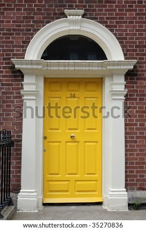 Yellow front door in urban street - stock photo