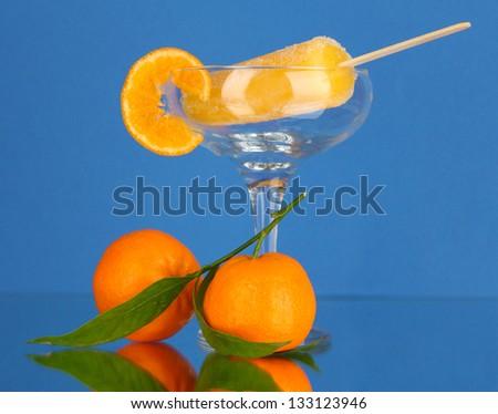 Yellow fruit juice ice in vase on blue background - stock photo