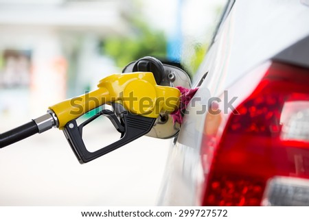 Yellow fuel nozzle at a gas station.