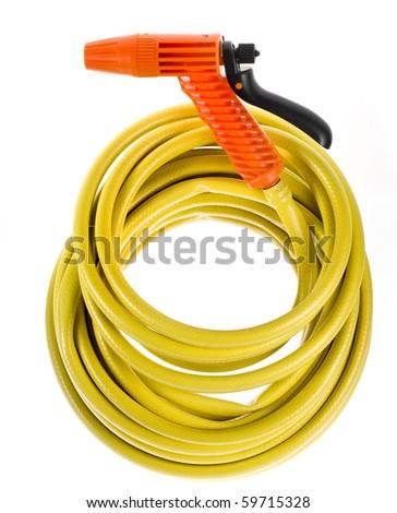 yellow garden hose coiled  with spray nozzle - stock photo