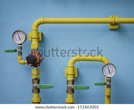 Yellow gas meter against blue wall - stock photo
