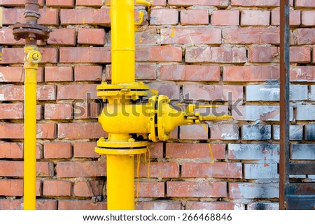 Yellow gas pipe and valve on red brick wall, copyspace - stock photo