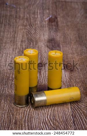 Yellow 20 gauge shotgun shells with wooden background - stock photo