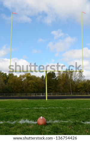 Yellow Goal Posts and Football on American Football Field - stock photo