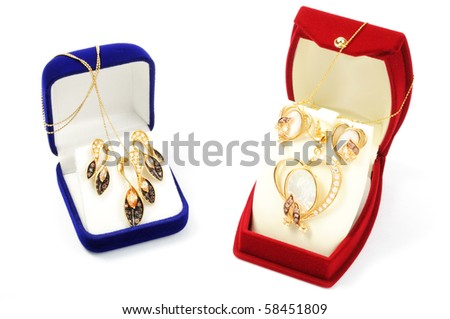 Yellow gold sets in open boxes, on white background