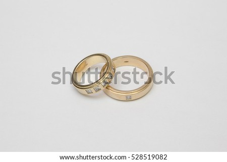 Yellow gold wedding rings with diamonds isolated on white.