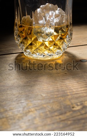 Yellow golden alcoholic drink with ice in a brandy glass, on a wood table