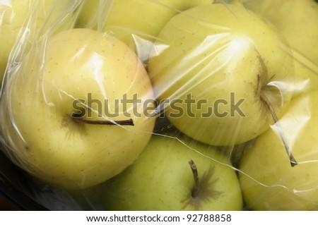 Yellow Golden Apples packed in plastic film, sold in bulk - stock photo