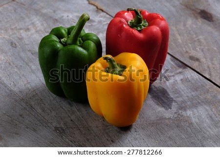 Yellow Green and Red Pepper Capsicum on Wooden Background - stock photo