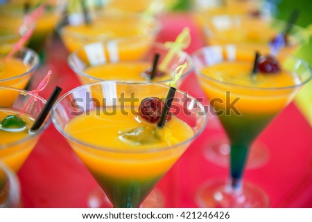 yellow green cocktail with cherry and drinking straw in summer