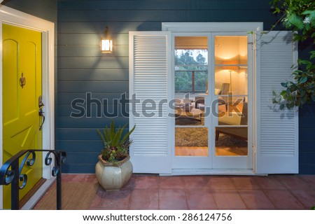 Yellow Green entry door / front door with glimpse into living room interior at twilight.  - stock photo