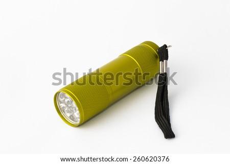Yellow-green led aluminum flashlight on a white background - stock photo
