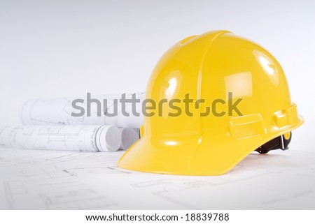 Yellow hard hat and blueprints in a construction concept - stock photo