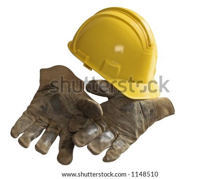 Yellow hard hat on well-used work gloves - stock photo