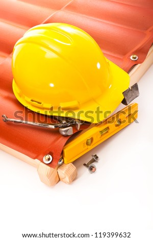 Yellow hard hat, pliers, screws, scrap, and the level of the roof with a wooden frame