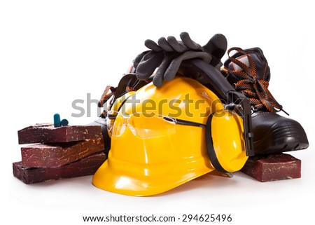 Yellow hardhat, headphones against noise, facing stone, boots and gloves on a white background - stock photo