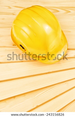 Yellow hardhat on pine wood planks as copy space for carpentry job concept, top view - stock photo