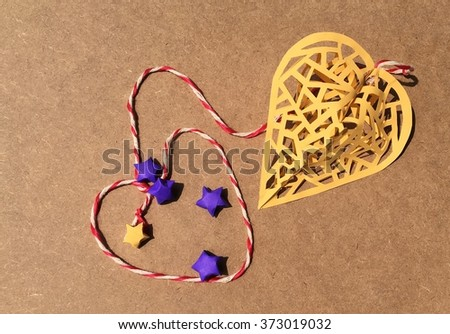 yellow heart cage with stars - paper cutting art on plywood background