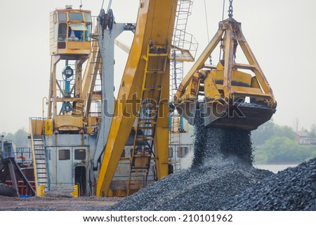 Yellow heavy excavator and bulldozer unloading road metal during road work  - stock photo