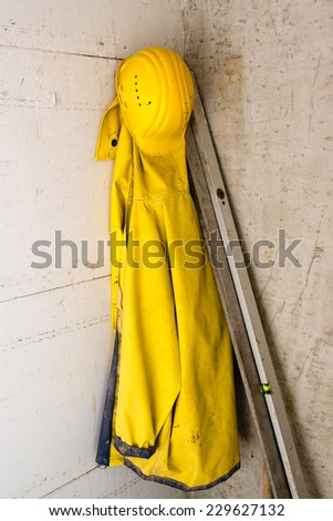 yellow helmet and raincoat with tools on a construction site - stock photo