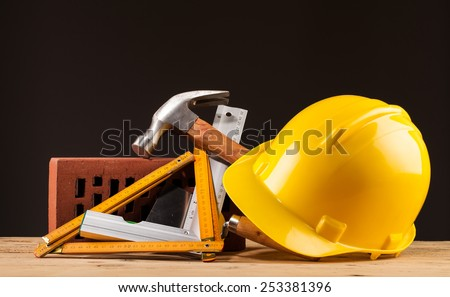 yellow helmet brick and builder tools on wooden table - stock photo