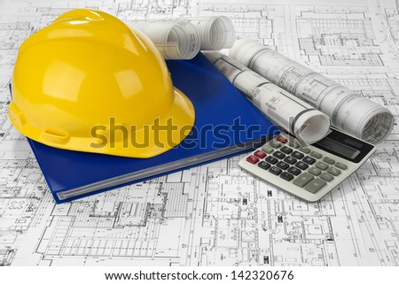Yellow helmet, calculator, blue folder document and project drawings - stock photo