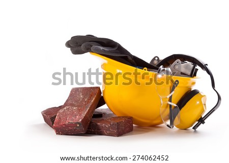 Yellow helmet, headphones against noise, goggles, gloves and stone cladding on a white background - stock photo