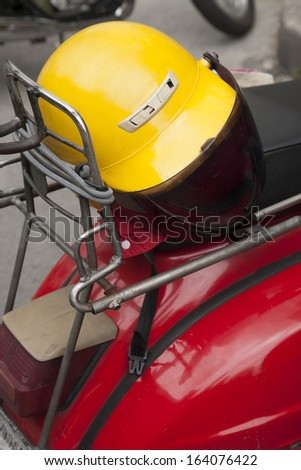 Yellow helmet on red scooter,close up - stock photo