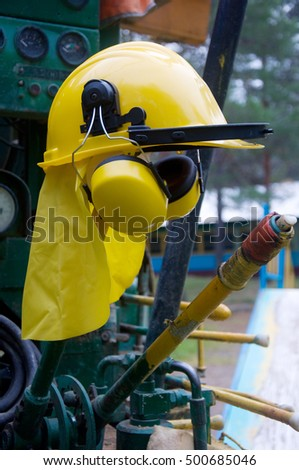 yellow helmet with headphones on a drilling machine