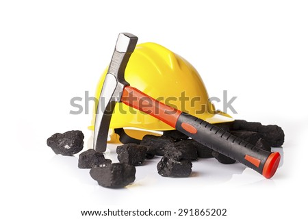 Yellow helmet with mining pickax and loose lumps of black coal on white background - stock photo