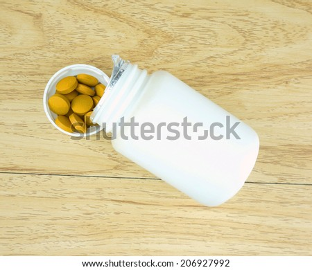 Yellow herbal pills was poured out of a bottle placed in the lid.                                - stock photo