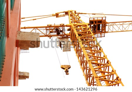 Yellow high construction crane and building site isolated on white