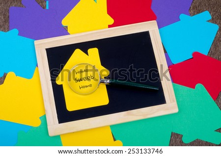 Yellow home sign with magnifying glass and blackboard: Home Sweet Home - stock photo