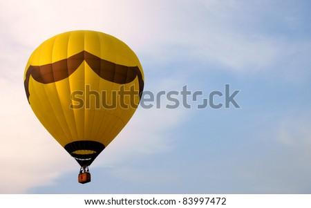 Yellow hot air balloon against a blue sky - stock photo