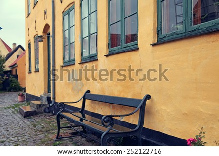Yellow house and bench in countryside in Denmark - stock photo