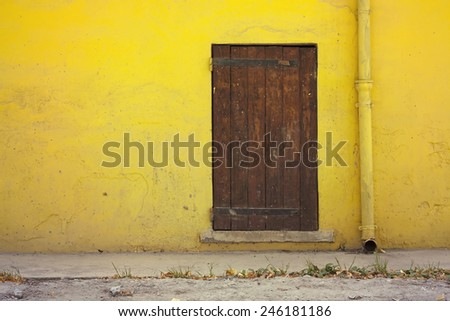 Yellow house wall and an old wooden door - stock photo