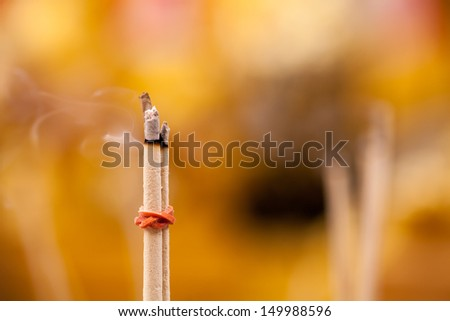 Yellow incense sticks burning in thai temple - stock photo
