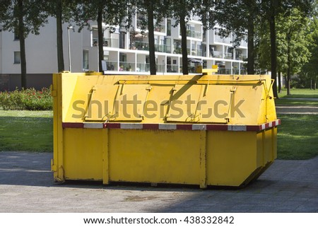 Yellow industrial garbage skip in a street in Rotterdam in the Netherlands - stock photo
