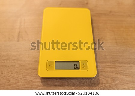 Yellow kitchen scale showing 0g at display.