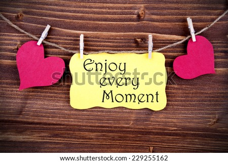 Yellow Lable Saying Enjoy Every Moment On Wooden Background Hanging On A Line, Two Red Heart Symbols; On Yellow Label; Background Is Old Fashion - stock photo