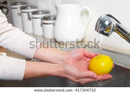 Yellow lemon in the sink. Fresh lemon - stock photo