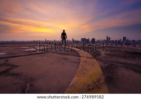 Yellow line lead to a man standing on the concrete floor of a skyscraper rooftop building watch a city sunset  - stock photo