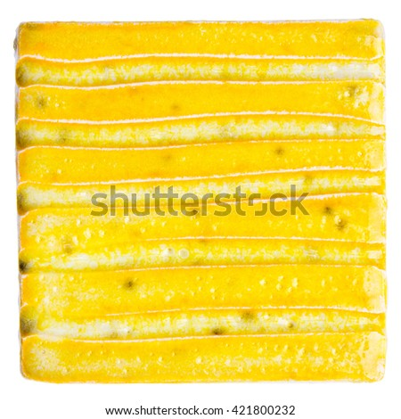 Yellow lined handmade glazed ceramic tile isolated on white background - stock photo