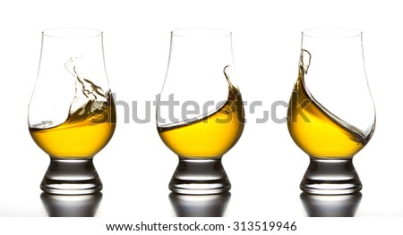 Yellow liquor in whiskey glass splash