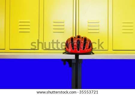 Yellow locker room doors and a bicycle helmet - stock photo