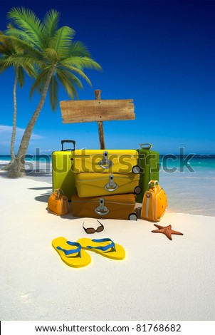 Yellow luggage, a blank wooden sign and thongs on a tropical beach - stock photo