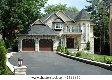 Yellow luxury home with railing, double front doors and stonework - stock photo